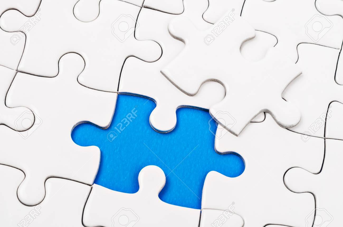Plain white jigsaw puzzle, on blue background. - 75626347