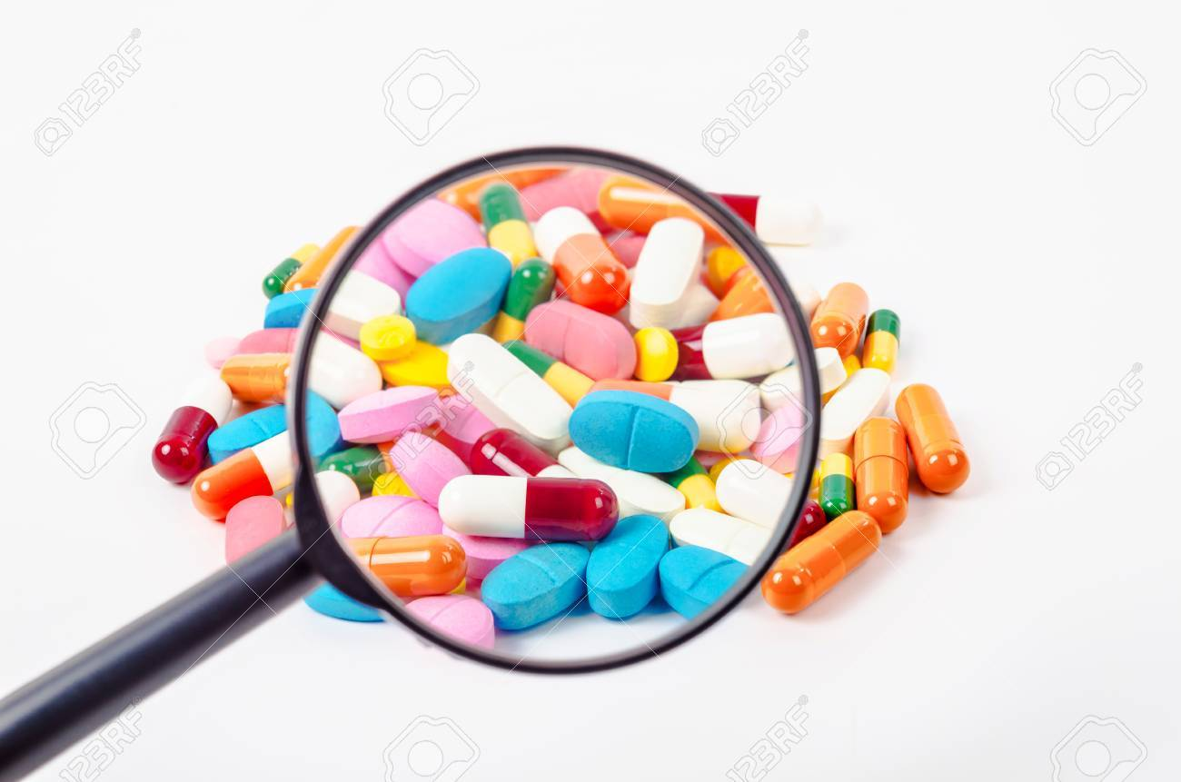 pills under magnifying glass on white background. - 87488282