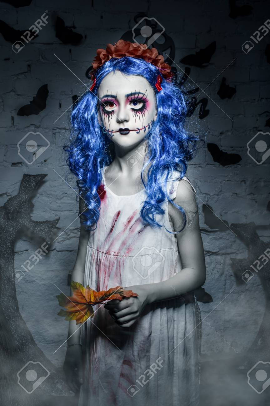 little blue hair girl with scary halloween makeup is holding.. stock