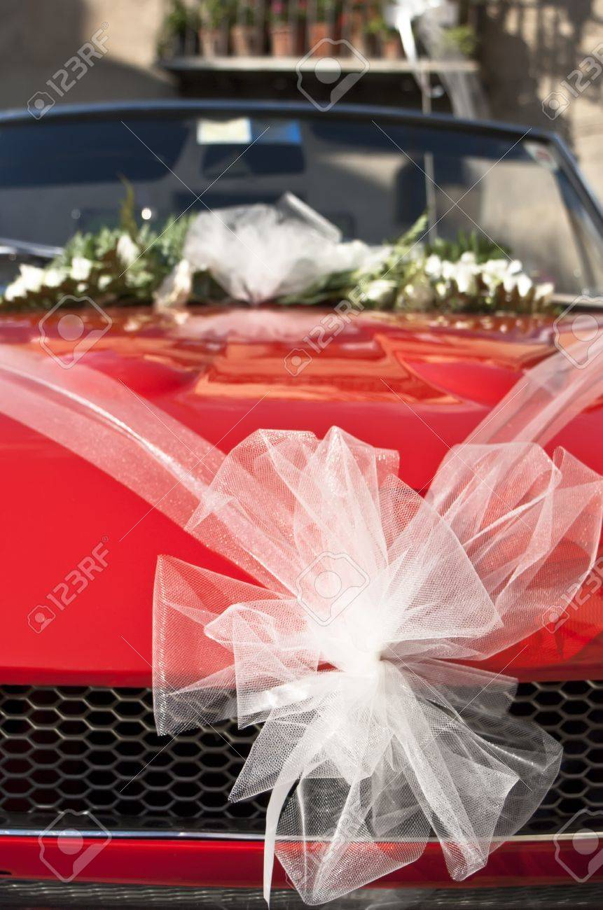 Red Wedding Car With White Ribbon And Flowers On The Windshield ...
