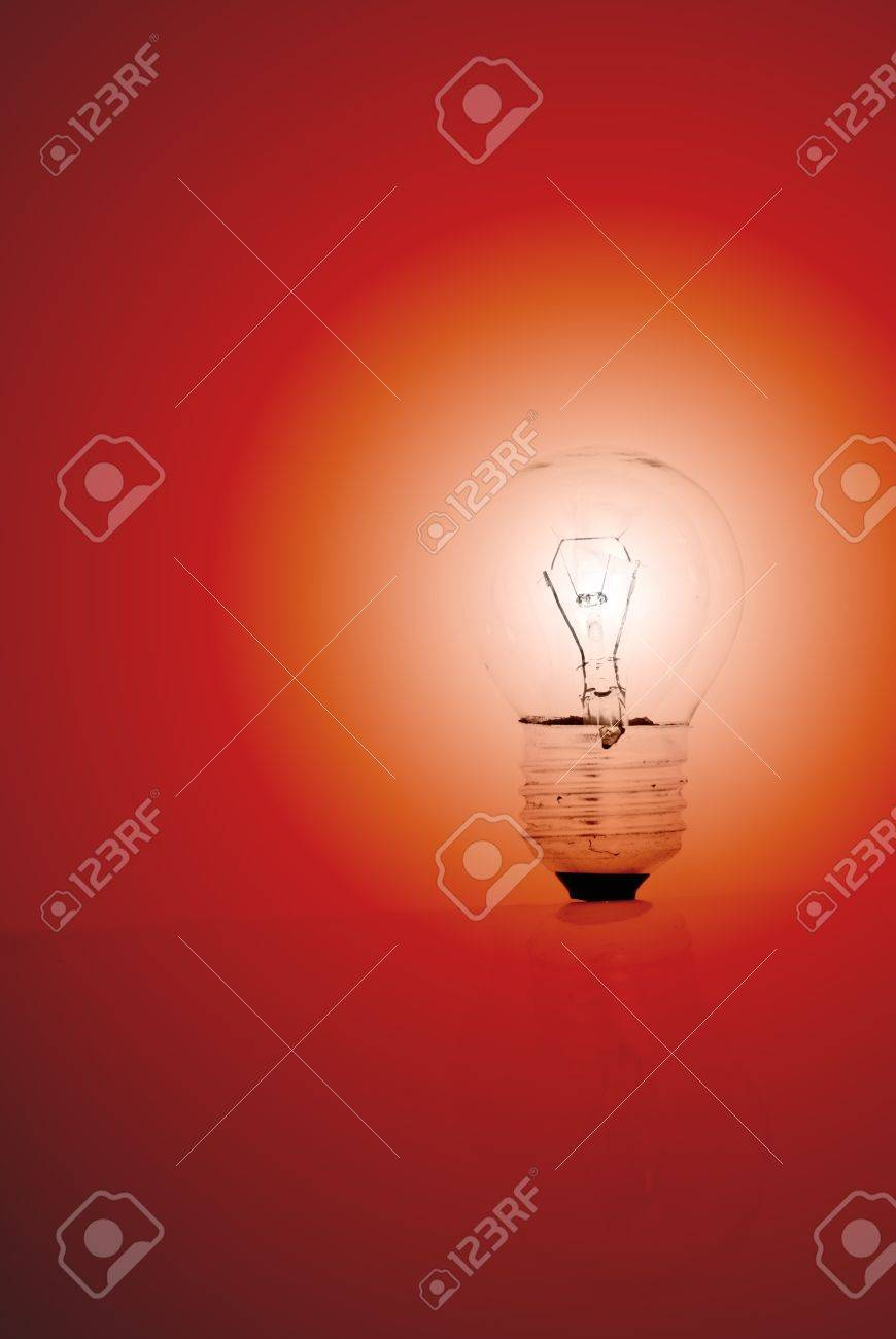 A lit light bulb on a red background. Stock Photo - 14616355