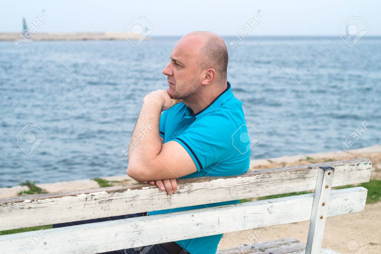 A man sitting on the bench and looking at the sea - 34562884