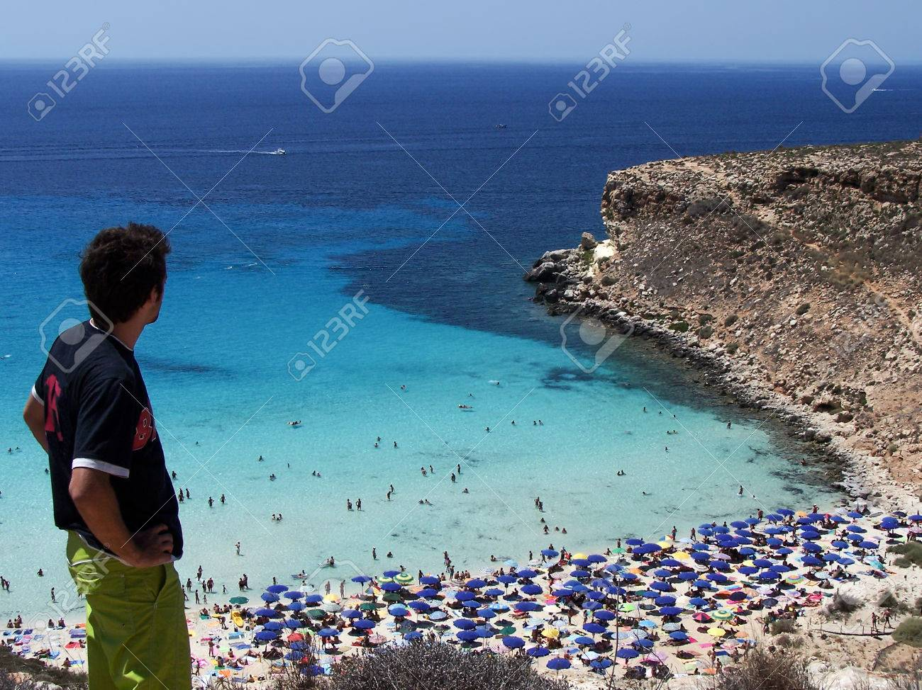 Young Tourist Looks At The Magnificent Beach Of Rabbits In Lampedusa