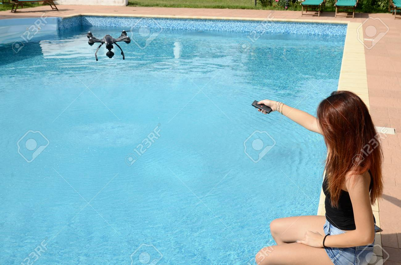 girl fly drone with remote control by the swimming pool