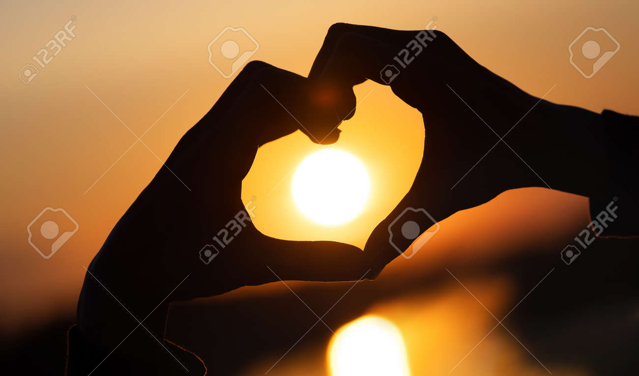 silhouette hands forming a heart shape with sunset and reflection of a solar track in the water - 150329143