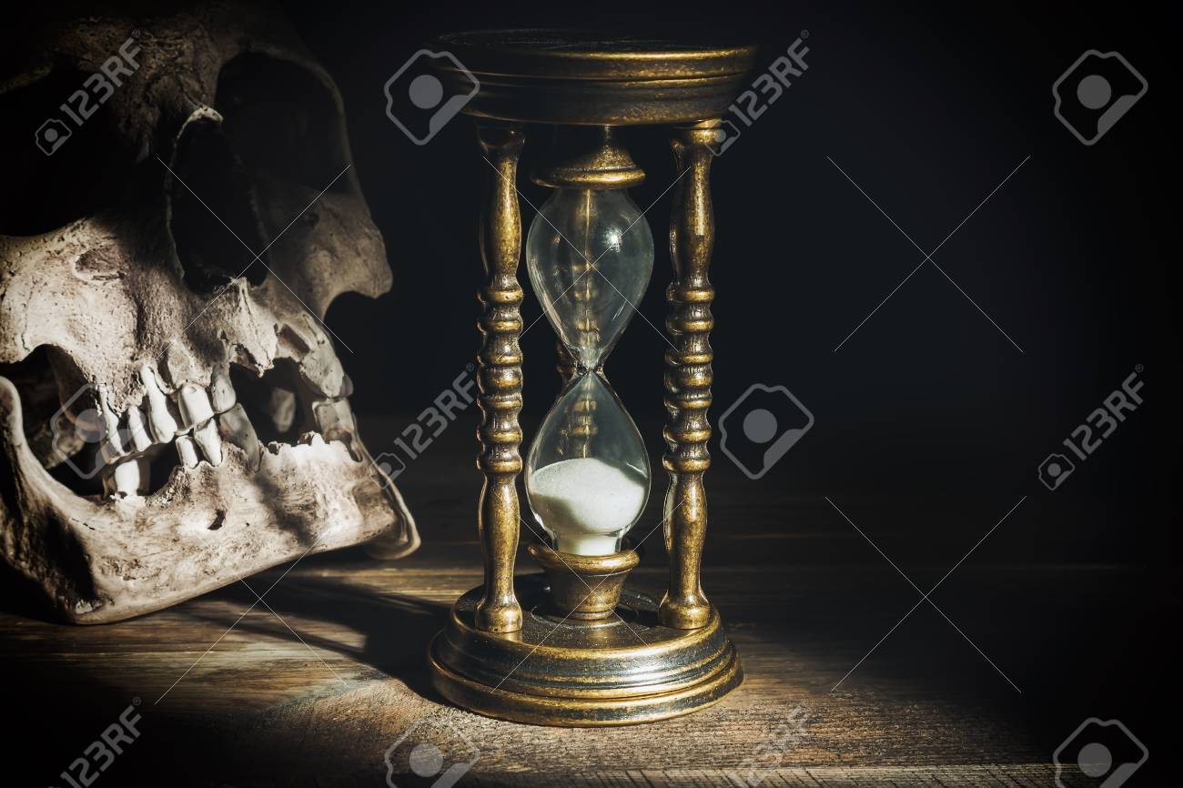 Skull and vintage hourglass on wooden background under beam of light. Stock  Photo - 87589184