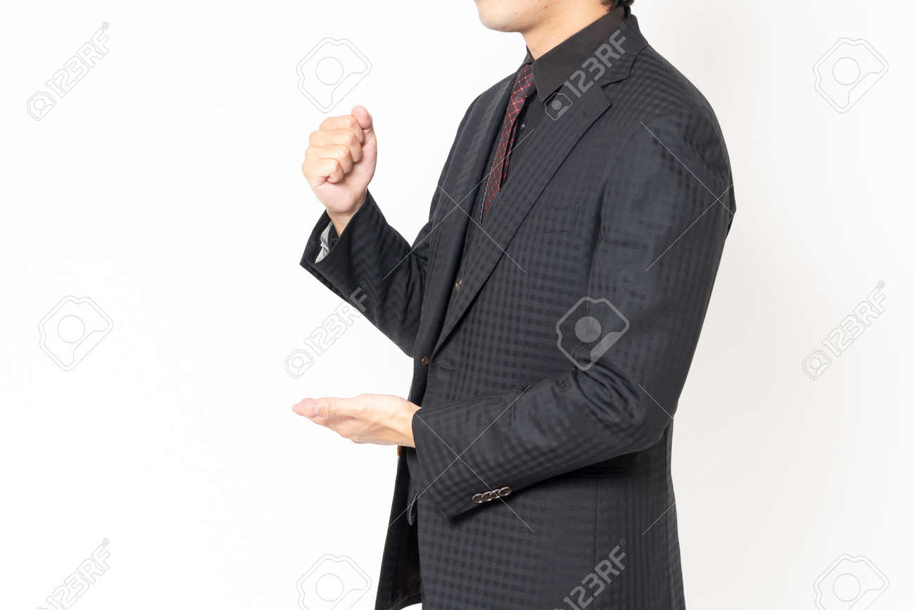 A male businessman standing in front of a white background and making a convincing gesture - 168586812
