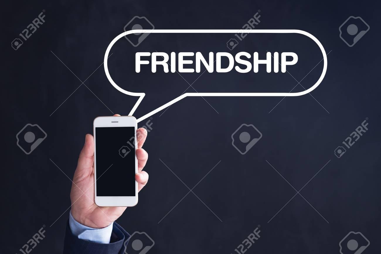 Hand Holding Smartphone with FRIENDSHIP written speech bubble
