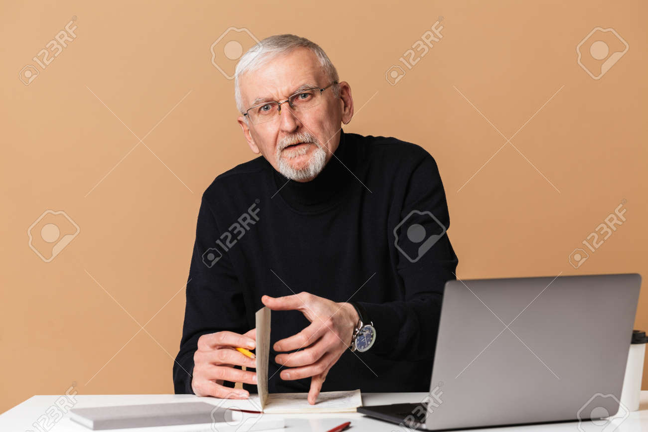 Old man with gray hair and beard in eyeglasses and sweater sitting at the table with laptop and notebook thoughtfully looking in camera over beige background isolated - 146290919