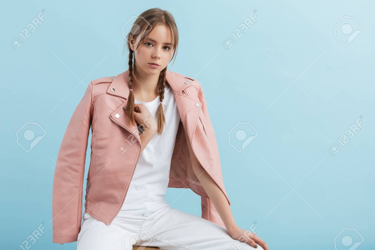 Young attractive pensive girl with two braids in pink leather jacket and white jeans dreamily looking in camera over blue background - 147593992