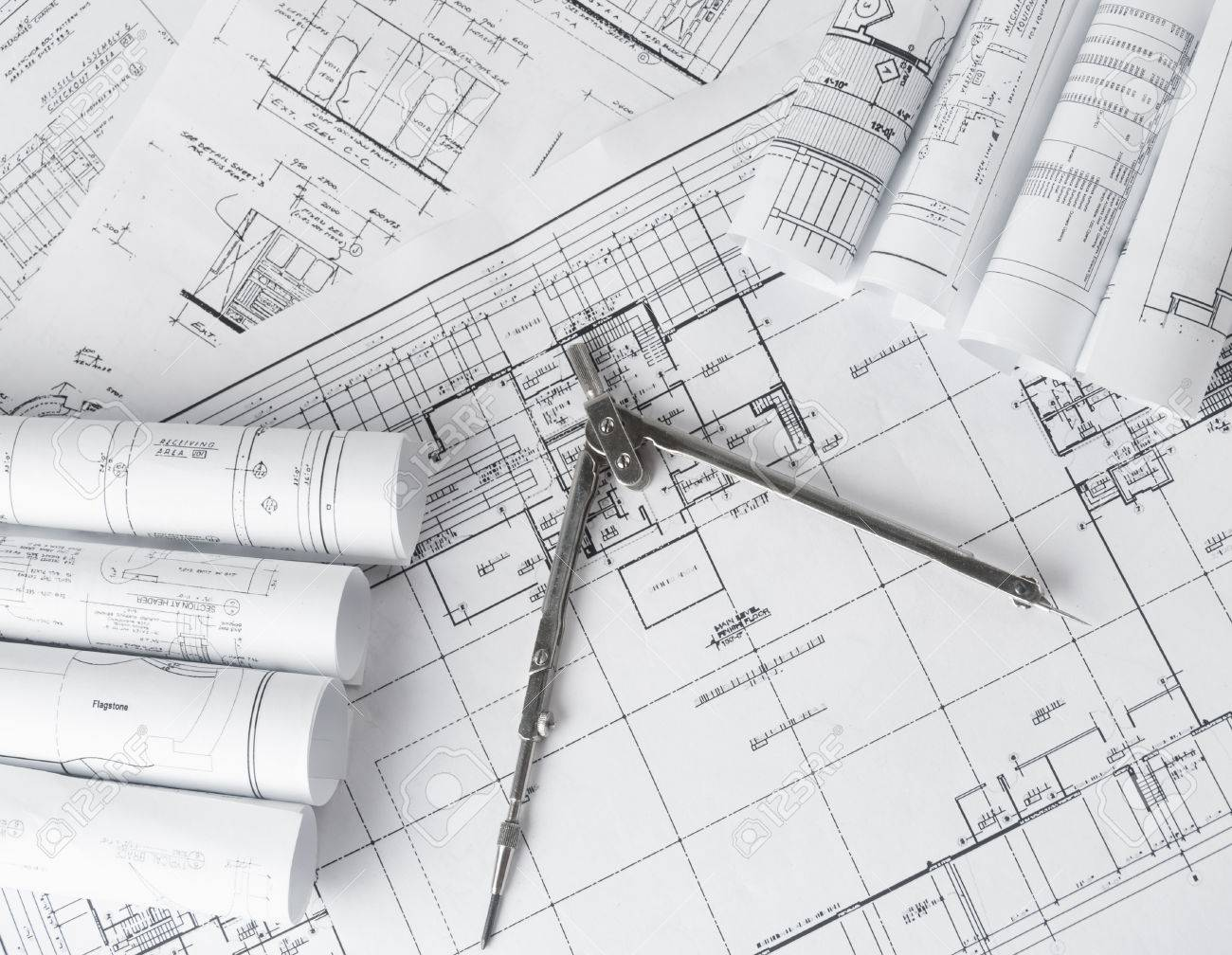 Rolls Of Architecture Blueprints And House Plans On The Table