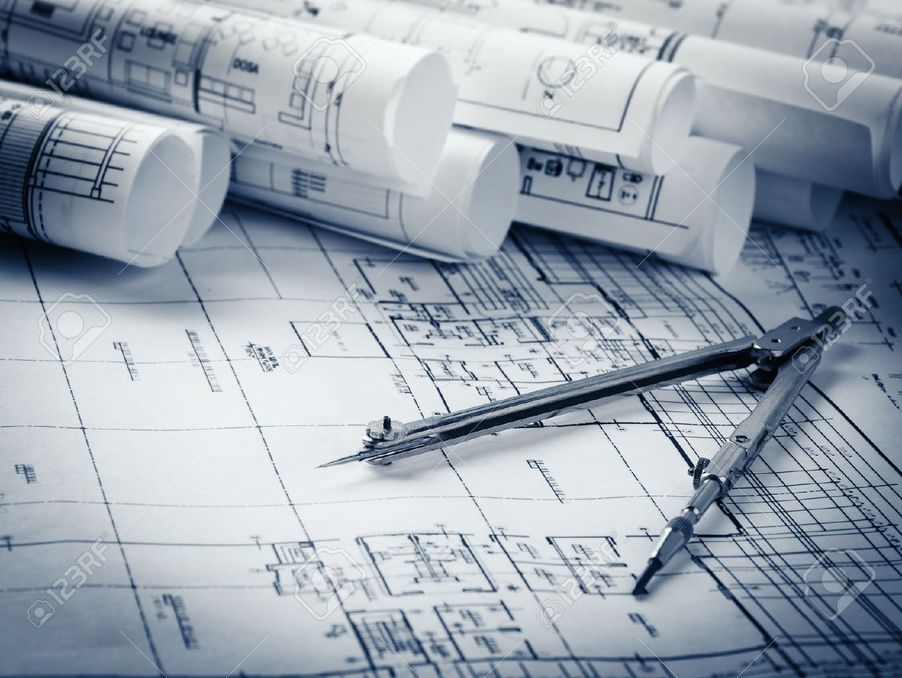 architecture blueprints. Rolls Of Architecture Blueprints And House Plans On The Table Drawing Compass Stock Photo - A