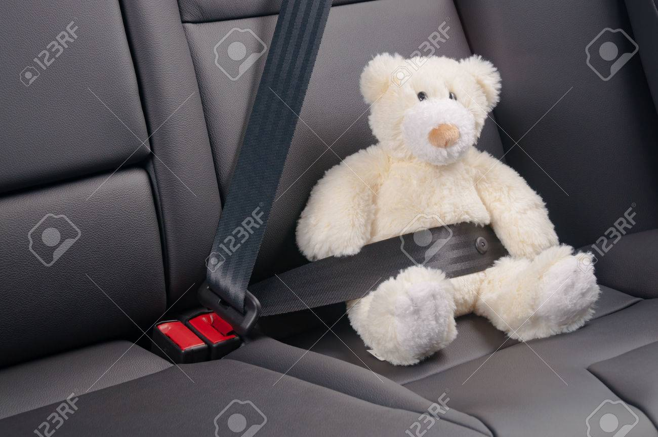 Teddy bear fastened in the back seat of a car, safety on the road - 47682160