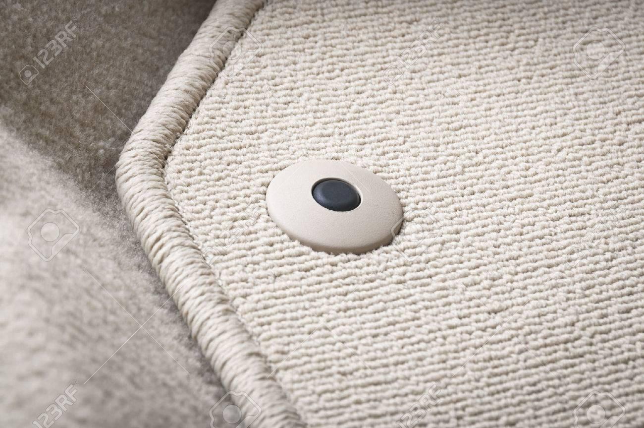 Corner of car mat with floor holder in white car interior - 57201380