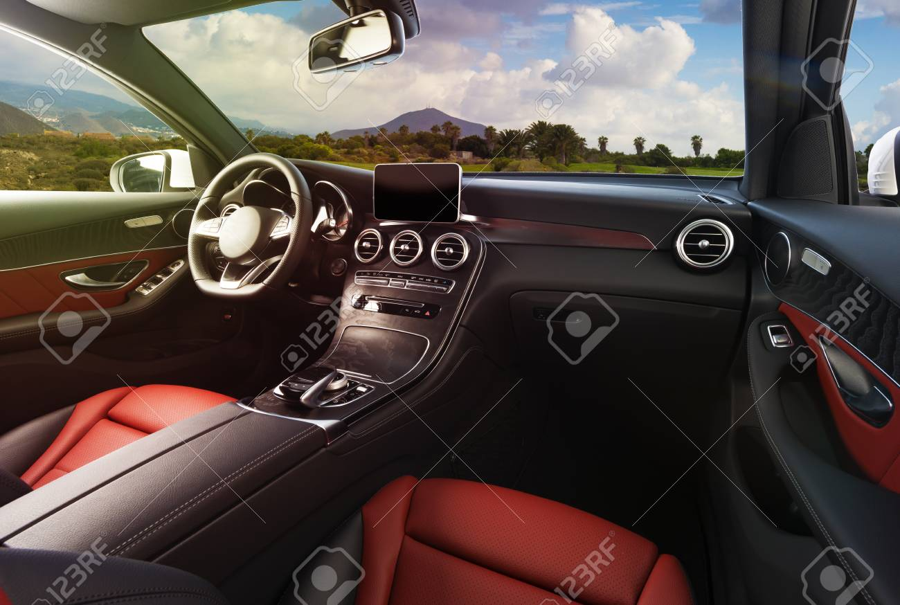 Modern luxury car Interior - steering wheel, shift lever and dashboard. Car interior luxury inside. Steering wheel, dashboard, speedometer, display. Red and black leather cockpit - 94293905