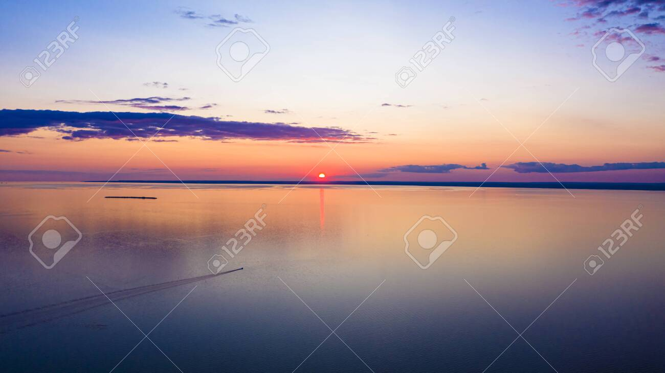 Sunset sky background. Dramatic gold sunset with evening sky clouds over the lake. Stunning sky clouds in the sunrise. Sky landscape. Panoramic view. - 138643177