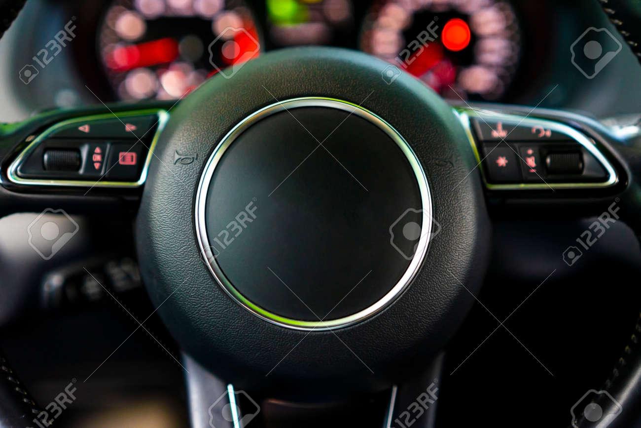 Modern luxury car Interior - steering wheel and blurred dashboard. Car interior luxury. Steering wheel, dashboard, speedometer, display. - 166244806