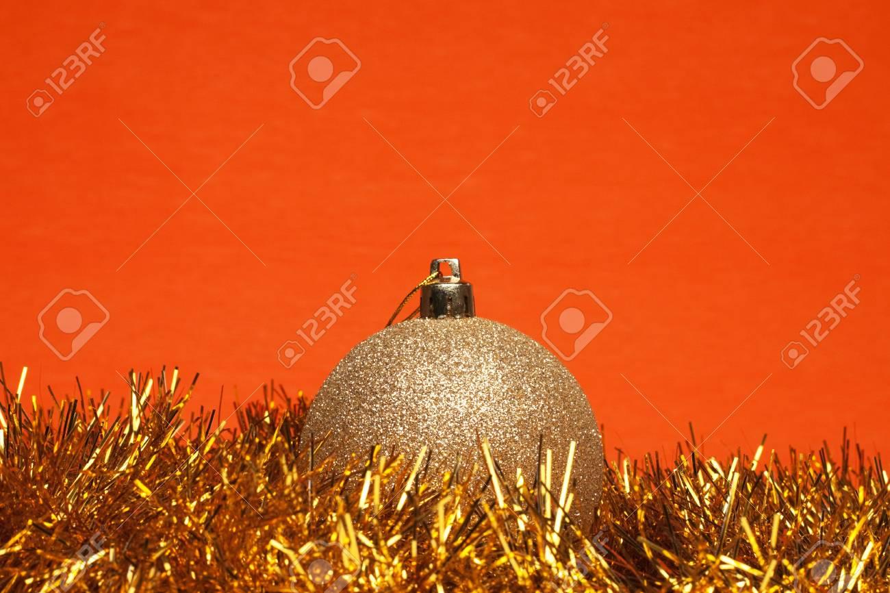 shiny christmas ball with tinsel over orange background Stock Photo - 8512604