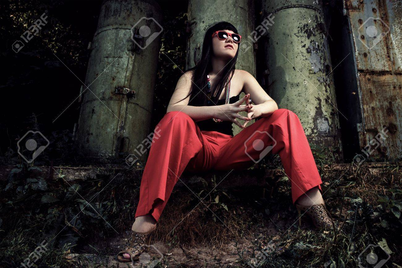 girl in red pants and glasses over industrial background Stock Photo - 15179000