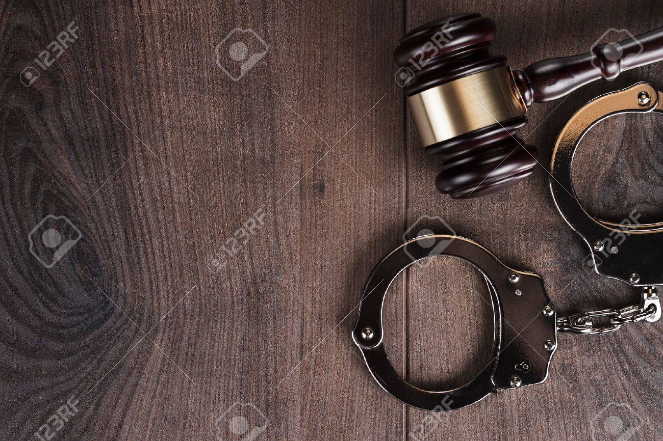 handcuffs and judge gavel on wooden background Stock Photo - 19450571