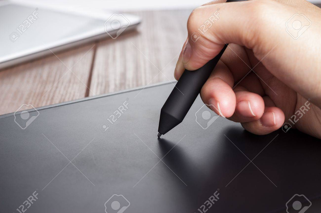 hand of the designer with a pen on tablet - 21070497