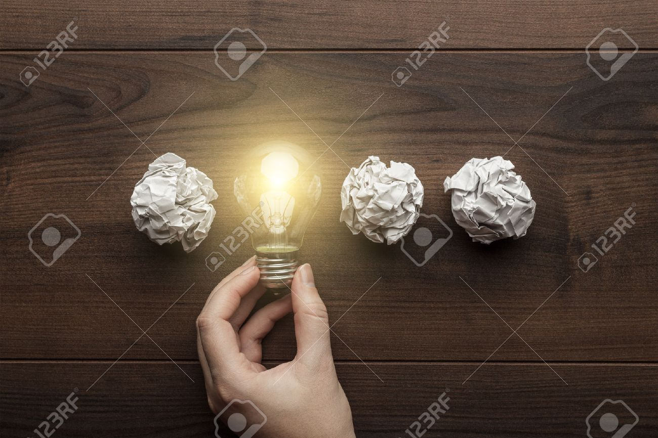 new idea concept with crumpled office paper, female hand holding light bulb - 37841102