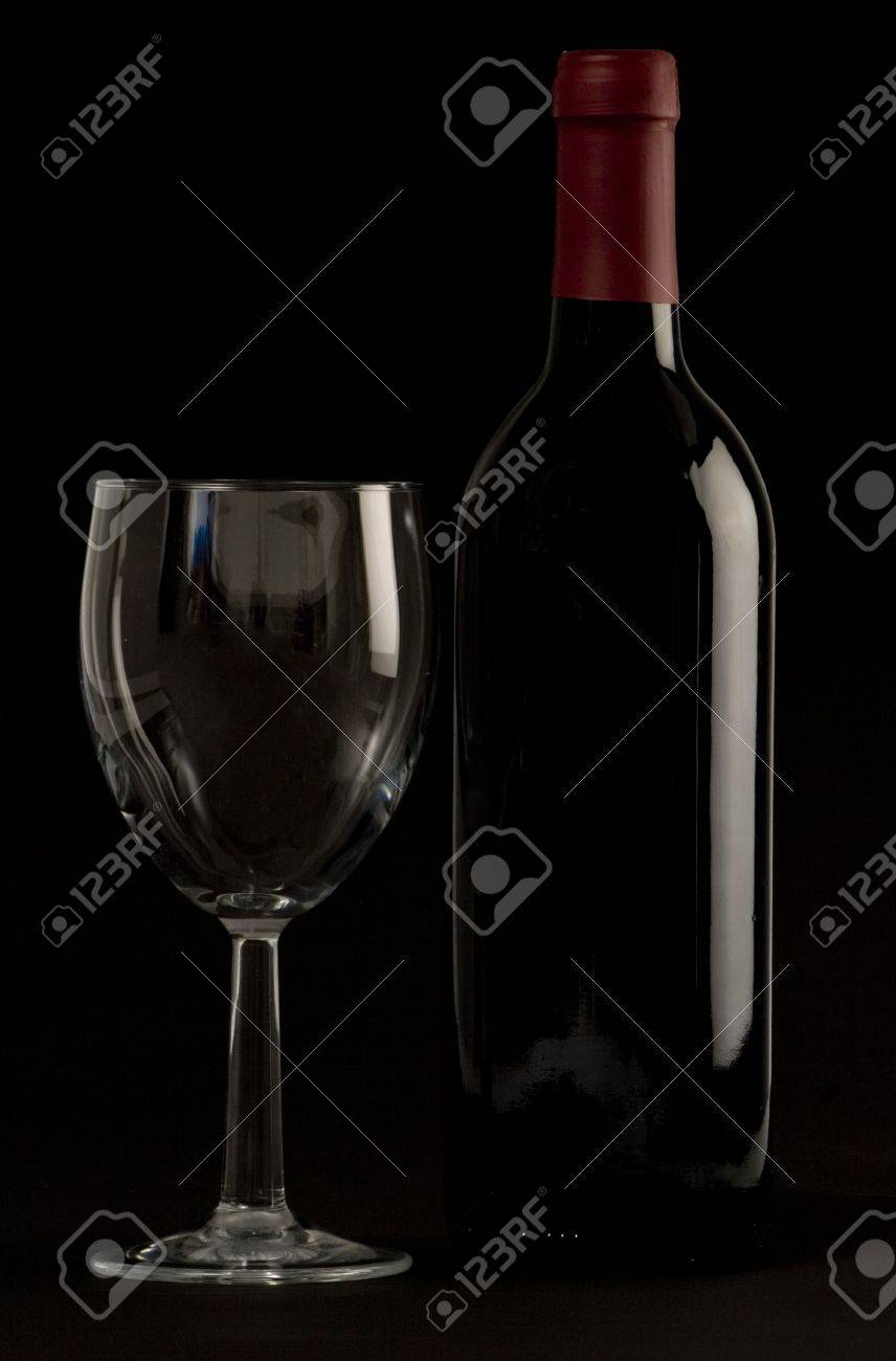 A Bottle of red wine with a wine glass on a plain background Stock Photo - 2038377