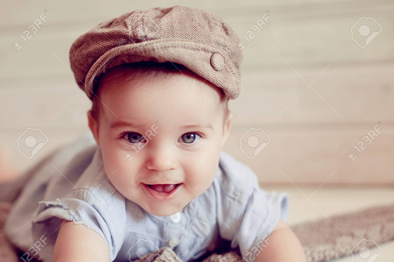 Adorable happy baby boy in a bright room. The baby in the hat smiling  looking d8e6a2c5e9a