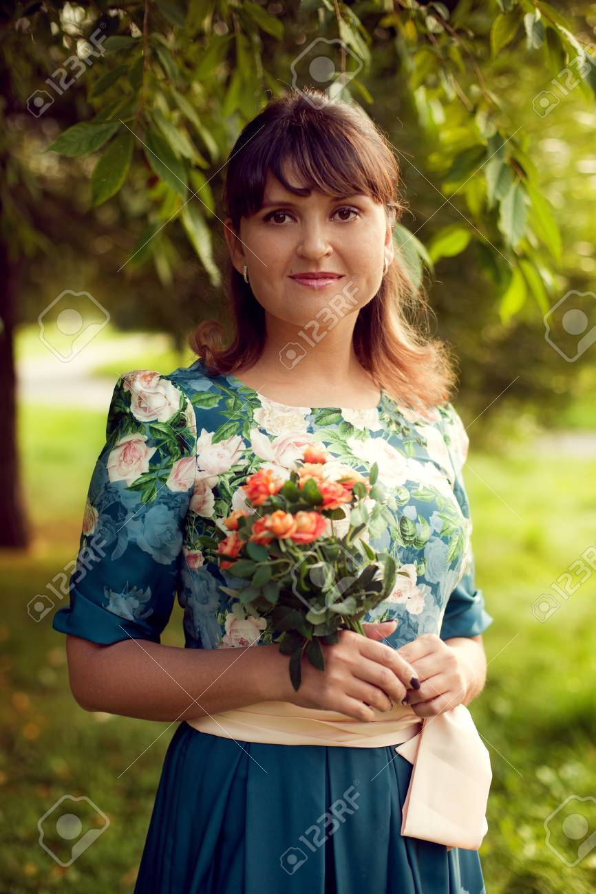 Young beautiful woman in floral dress posing in Park with a bouquet of flowers, on green background summer nature. - 66915686