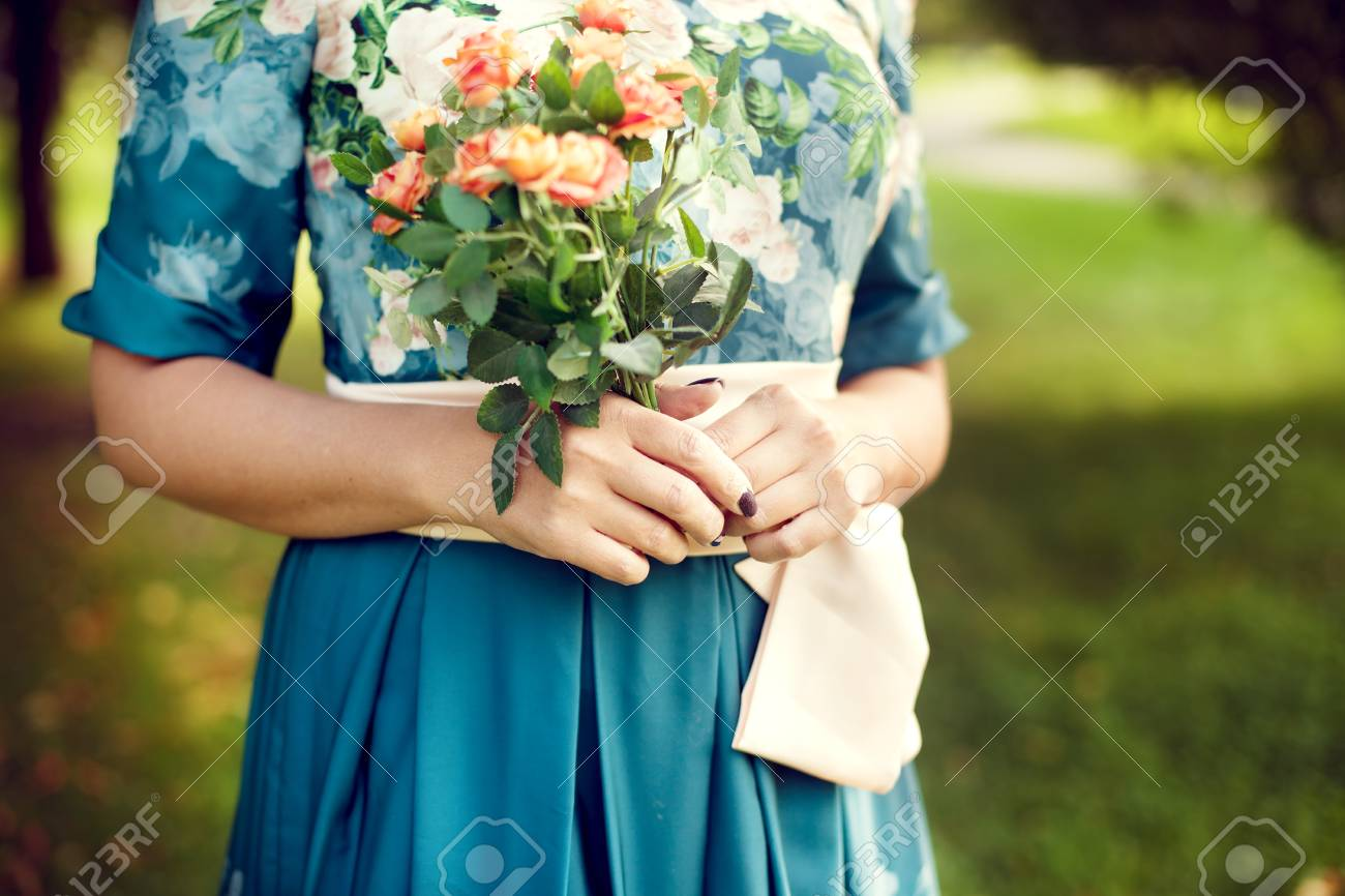 woman holding a bouquet of summer in the Park, floral dress, with a focus on flowers. Summer mood, holidays - 66915692