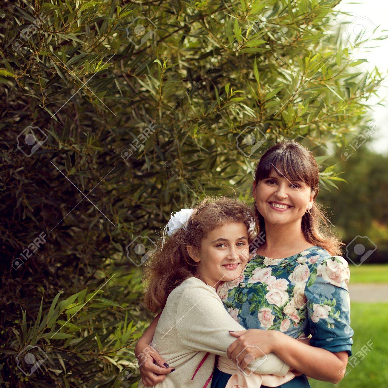 Beautiful young mother in a floral dress and daughter teen 10 years hugging in the Park in the summer, good family relationships - 66915733