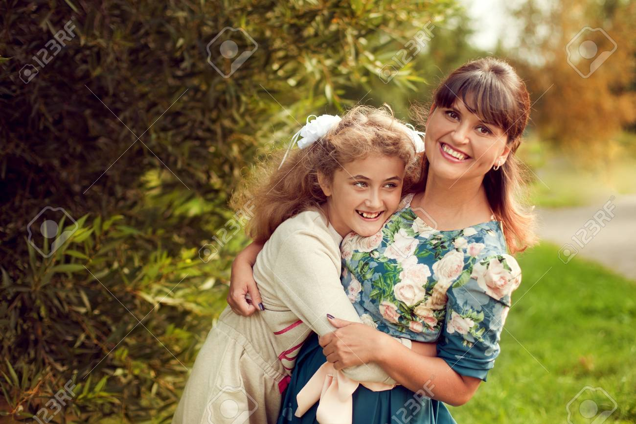 Beautiful young mother in a floral dress and daughter teen 10 years hugging in the Park in the summer, good family relationships - 66915752