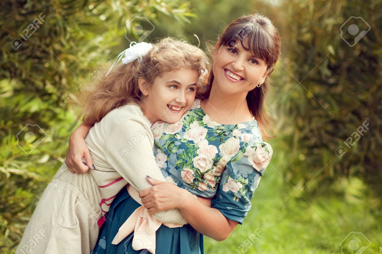 Beautiful young mother in a floral dress and daughter teen 10 years hugging in the Park in the summer, good family relationships - 66915757