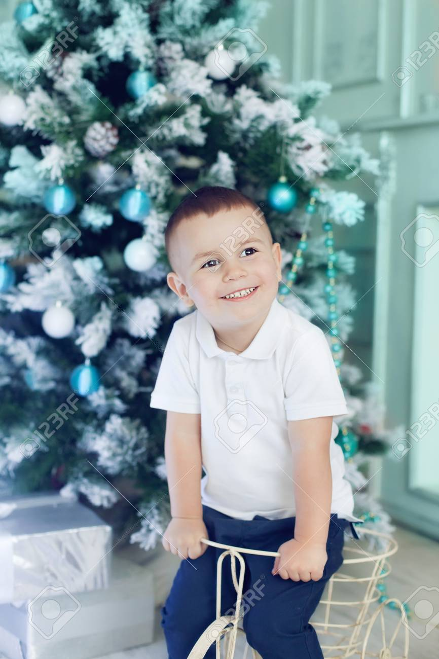Fun boy 3 years old playing in the room decorated for the Christmas tree. Beautiful Christmas interior in white and blue colours, happy kid waiting for presents - 66916176