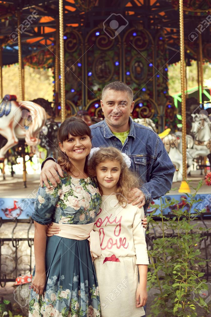 A normal happy family posing in the Park mom, dad and daughter 10 years fun walk in the summer Park - 66916421