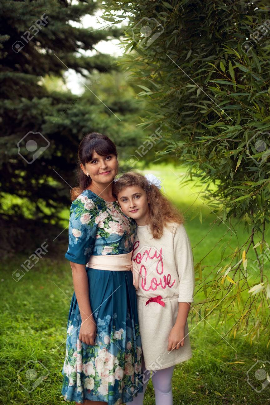 Happy family on a walk in the Park in the open air, mother and daughter 10 years hugging on green summer background - 66916483