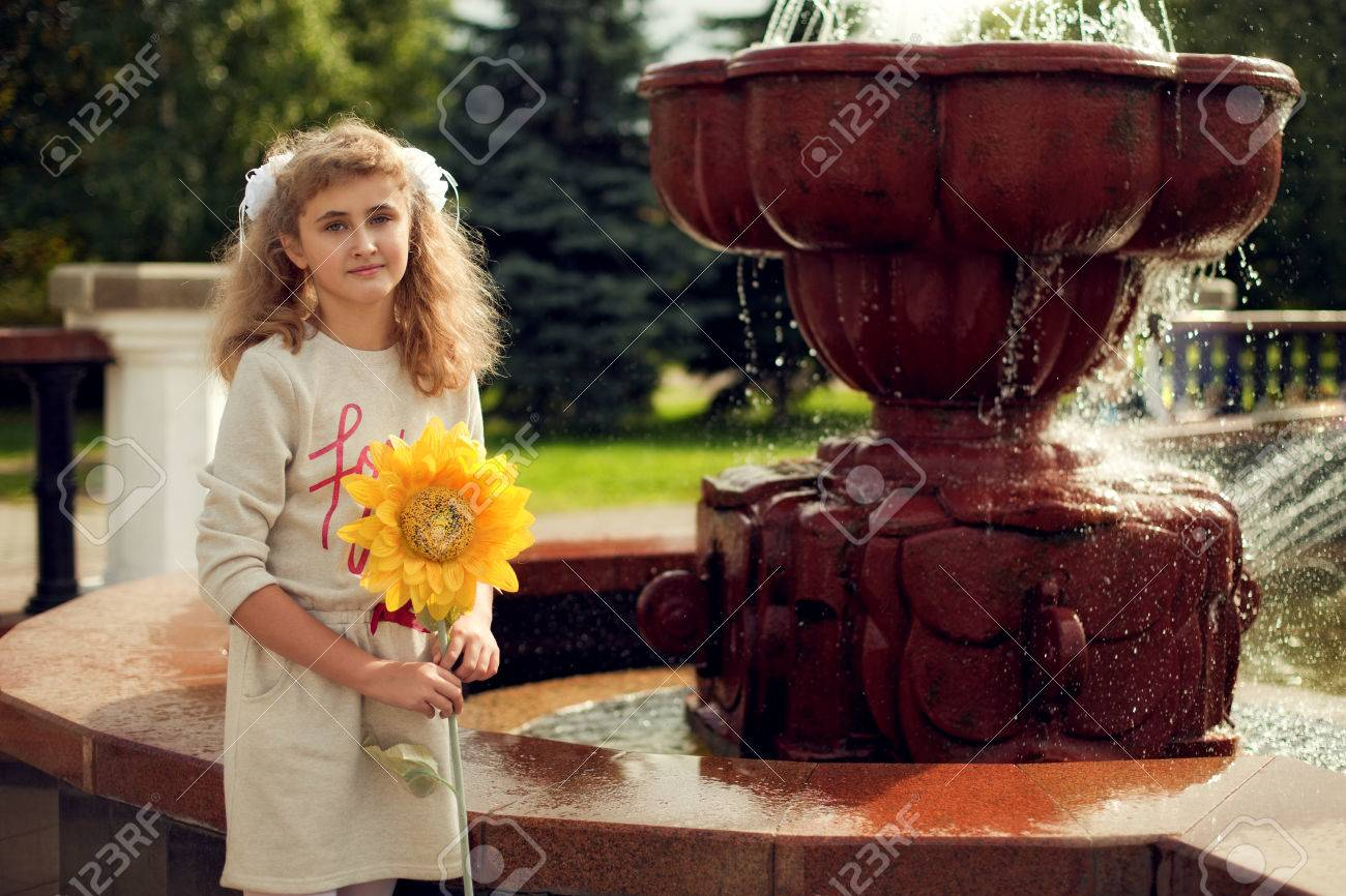 Beautiful 10 years old girl standing near a fountain, holding a sunflower walking around the city - 66916801