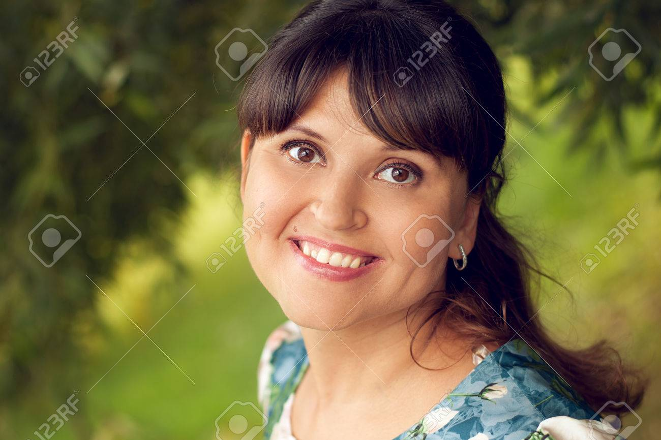 Beautiful happy young woman smiles white teeth, walking in summer Park - 66916822