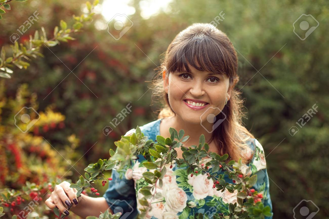 beautiful happy brunette woman in the park on a warm summer day, a girl in a floral dress walks outdoors - 66916837