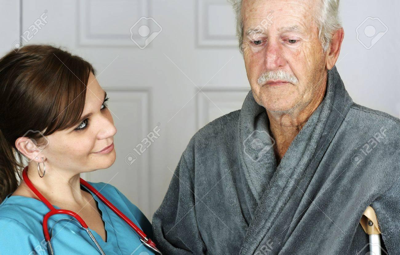 Nurse helping a senior man on crutches - horizontal Stock Photo - 5854235