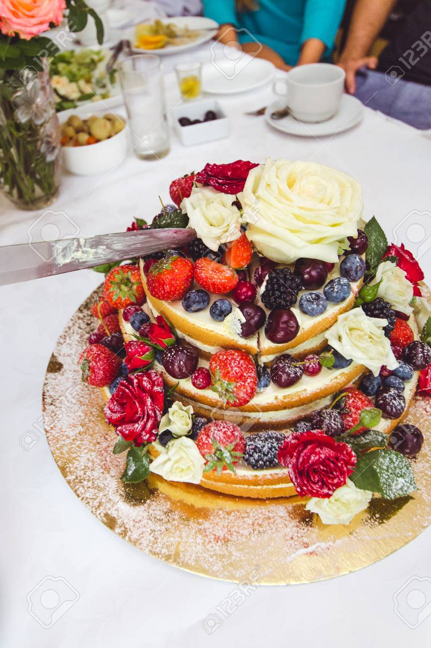 Tasty Wedding Cake With Fruits And Flowers On Table Stock Photo