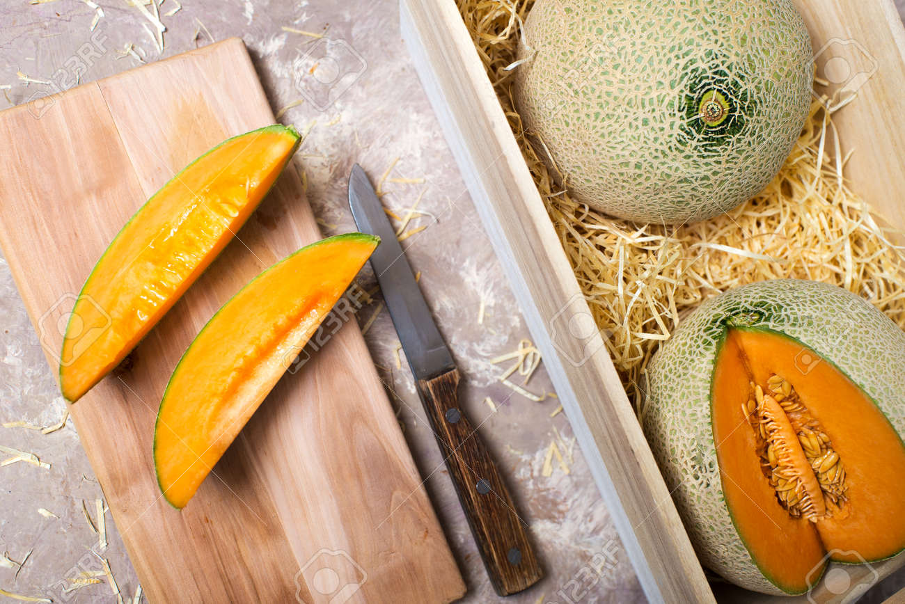 melons in a wooden box in straw. pieces of melon with a knife on the board. - 166002135