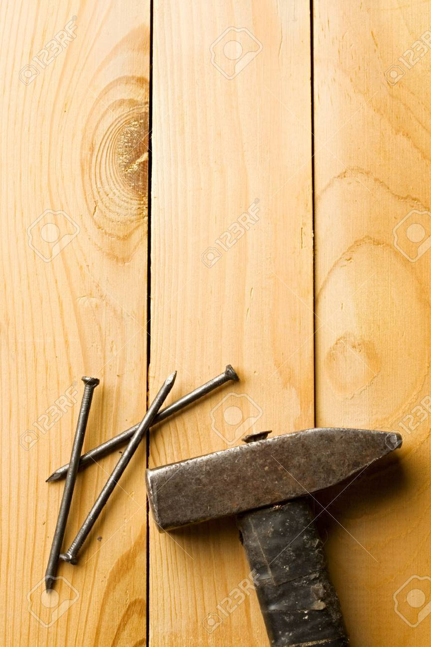 Hammer and nails isolated on wooden background Stock Photo - 8974033