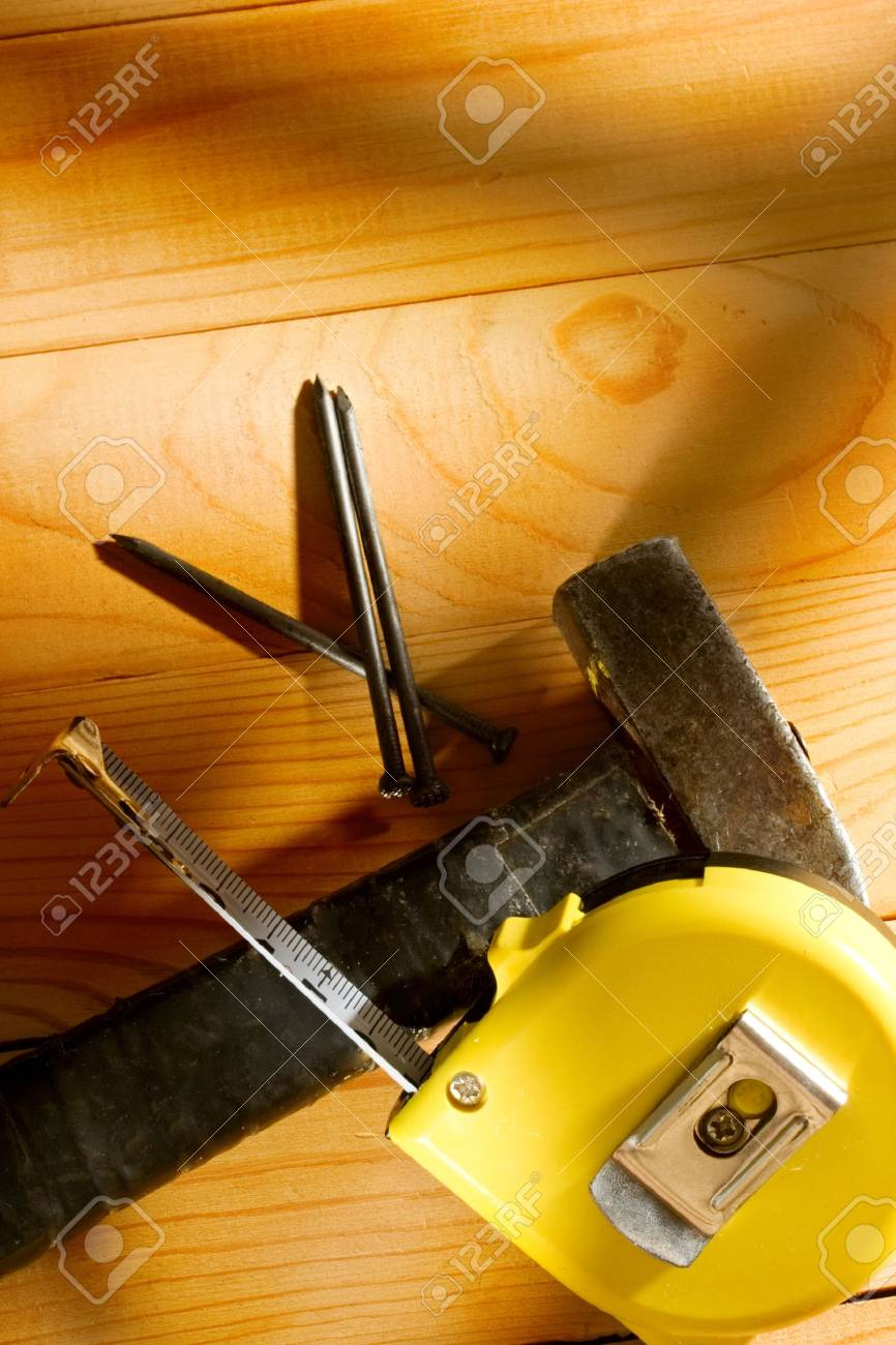 Hammer, tape measure and nails isolated on the wooden background Stock Photo - 10831405