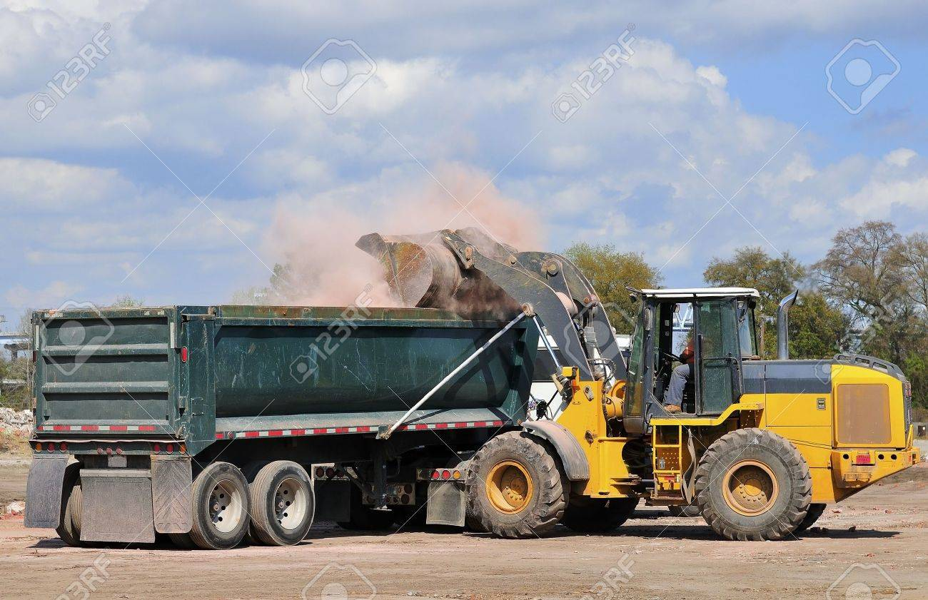 A large front end loader loading waste bricks into a dump truck stock photo 4619084