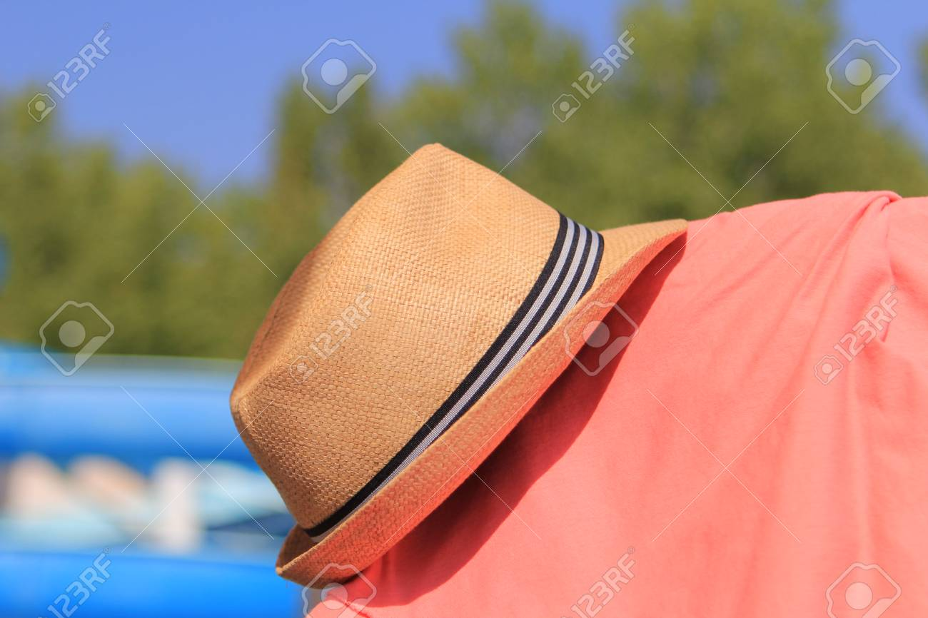 5513490a Straw trilby hat on sunny pool side with pink shirt Stock Photo - 64321631