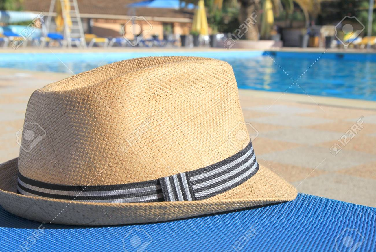 Stock Photo - Straw hat on a poolside sunlounger in early morning sunshine cdbb7a62dd77
