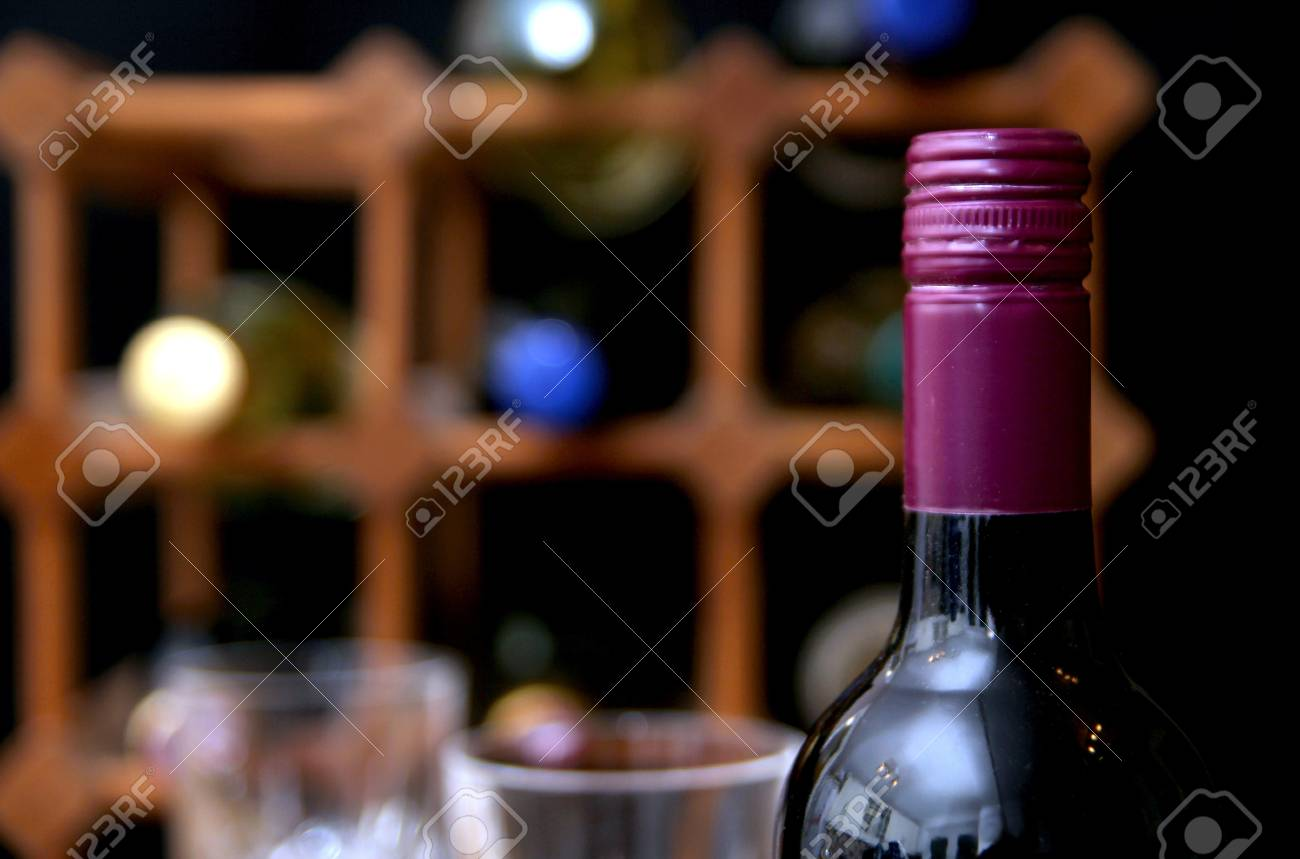 Closeup Of Burgundy Screw Top Wine Bottle With Wine Rack And Stock