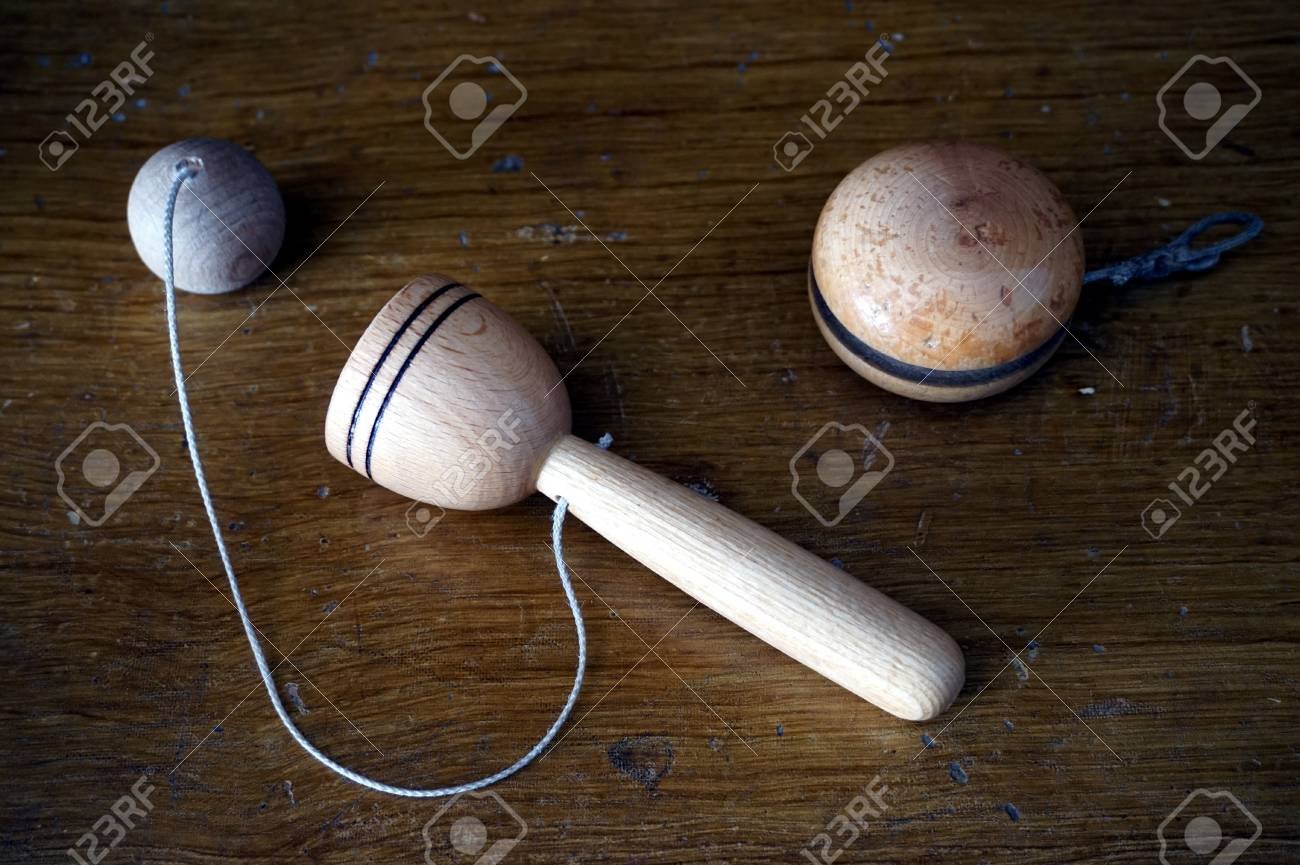old wooden child's toys, yoyo and ball catcher, on a vintage..