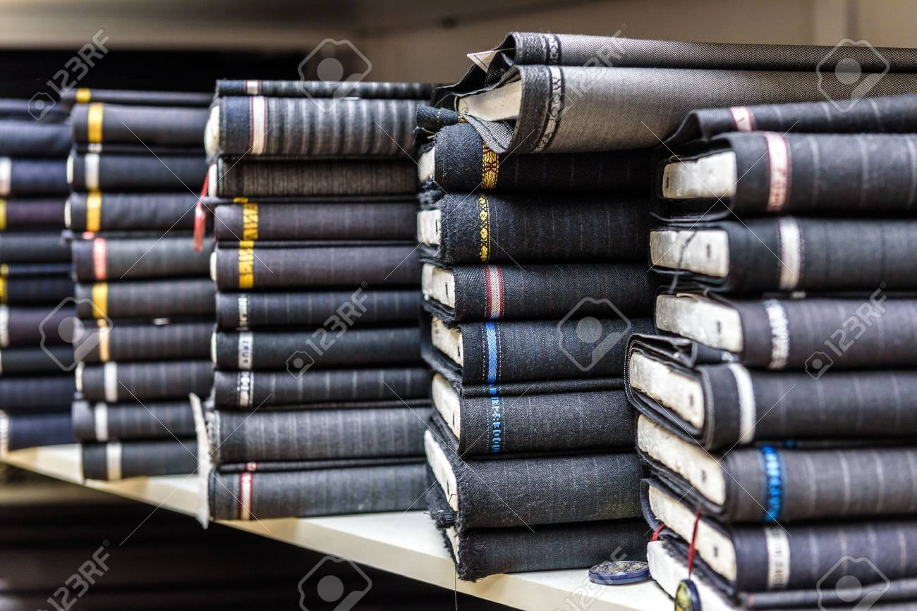 Rolls of fabric and textiles in a factory shop or store or bazar. Multi different fabric for men formal business suit on the market. Industrial fabrics. - 47547015